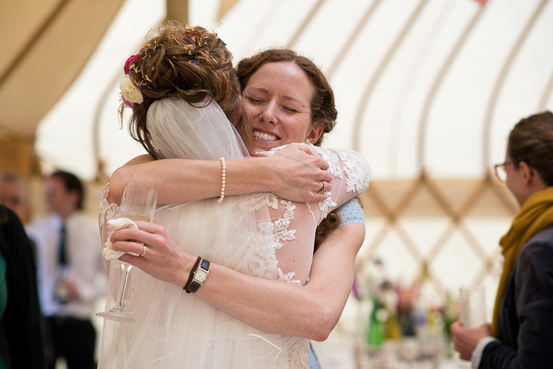 Bride hugs guests at yurt wedding