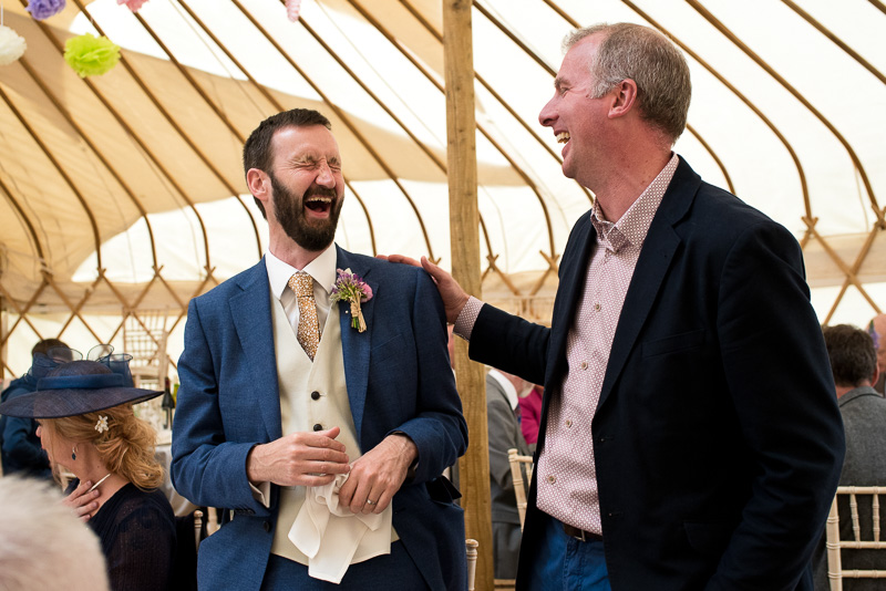 Groom laughing with guests at yurt wedding