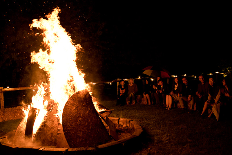 Guests sit around bonfire at North Hill Farm wedding