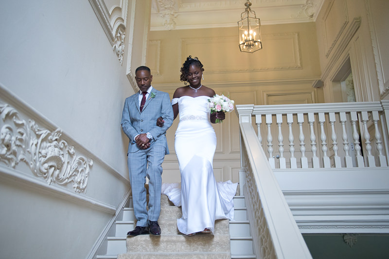 Black bride walks down the stairs at Morden Hall wedding
