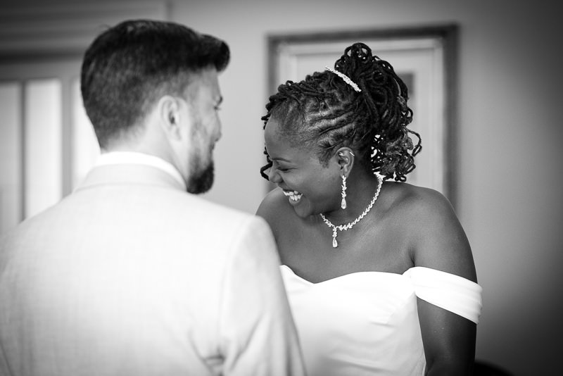 Bride and groom laugh together during Morden Hall wedding