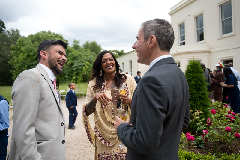 Indian groom mingles with guests at Morden Hall wedding