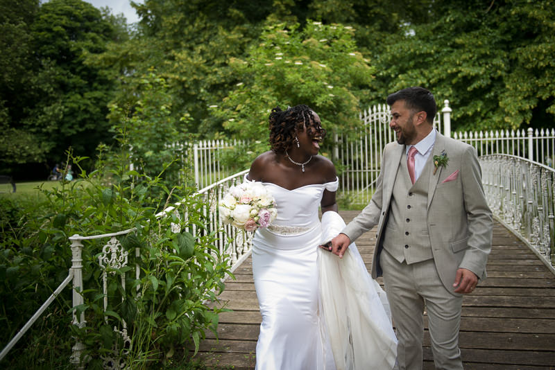 Bride and groom portrait on bridge at Morden Hall