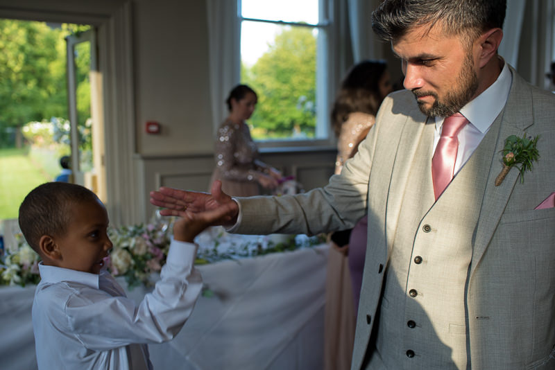 Groom gives boy high five at Morden Hall wedding