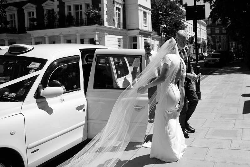 Bride with long veil arriving at St Pauls Onslow Square