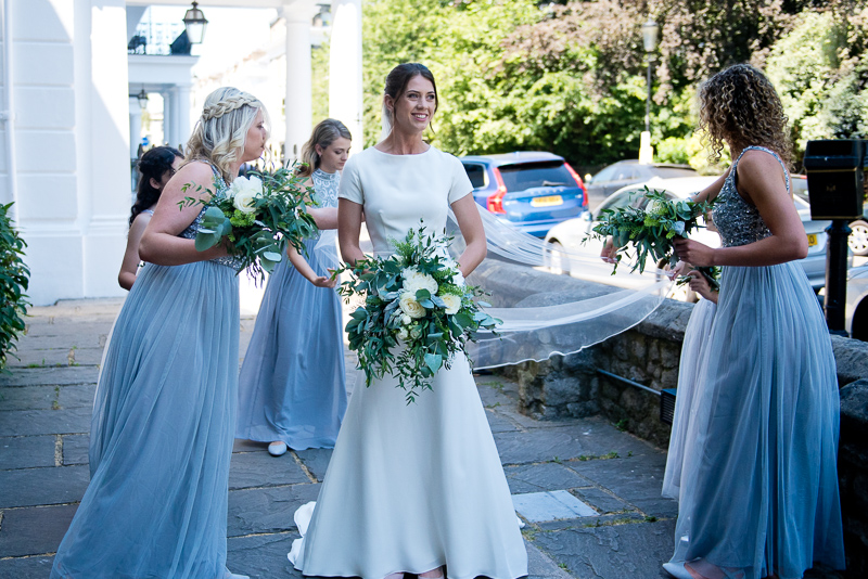 Bridesmaids adjusting bride's veil outside HTB Onslow Square
