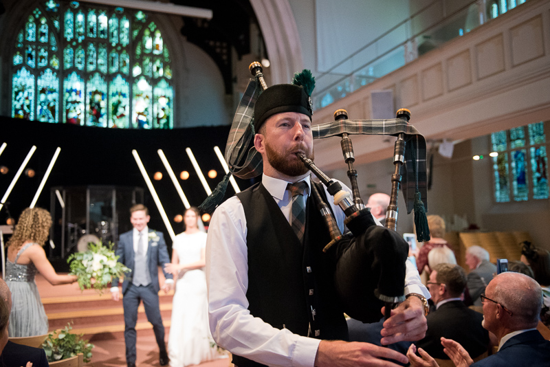 Bagpiper walking bride and groom down the aisle