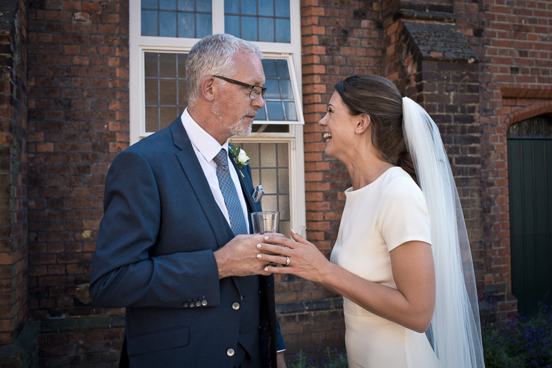 Bride with father during drinks reception at Fulham Palace wedding