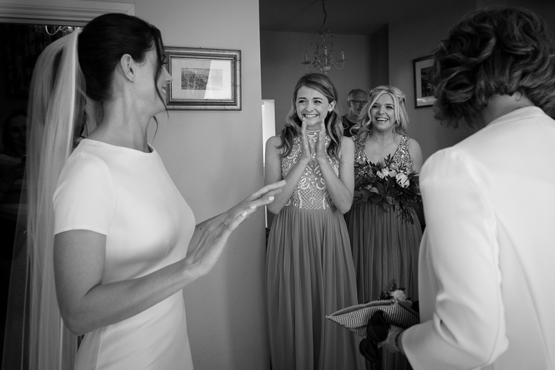 Black and white photograph of bridesmaids reacting to seeing Fulham Palace bride