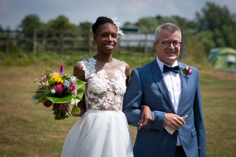 Bride arrives with father for outdoor wedding
