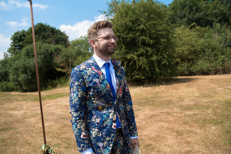 Groom watches bride arrive at outdoor wedding