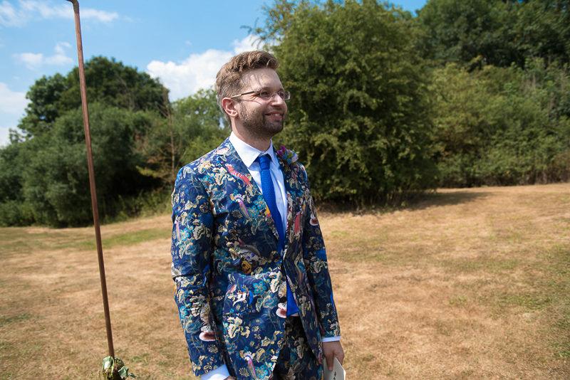 Groom watches bride arrive at outdoor wedding