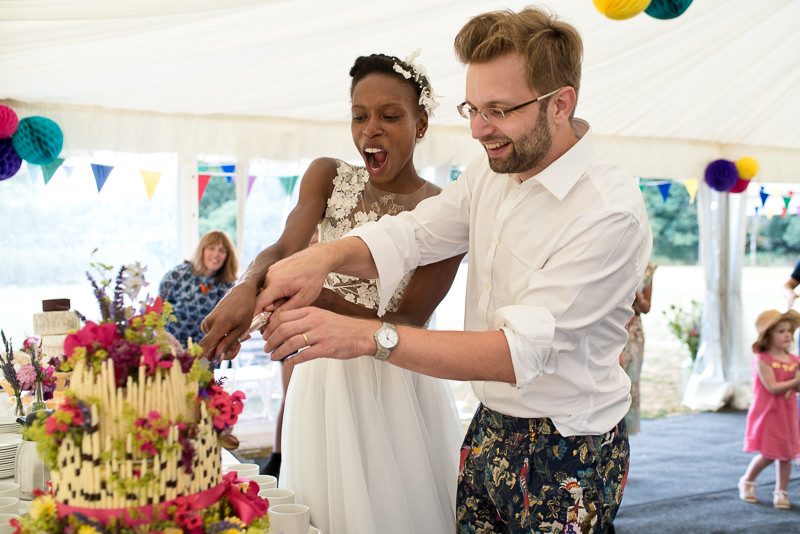 Bride and groom cut cake at outdoor wedding