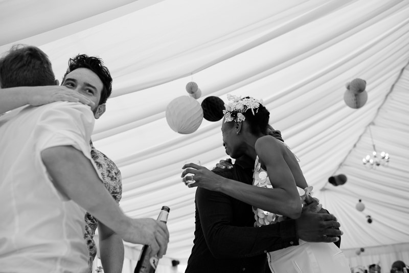 Bride and groom hug guests at outdoor wedding