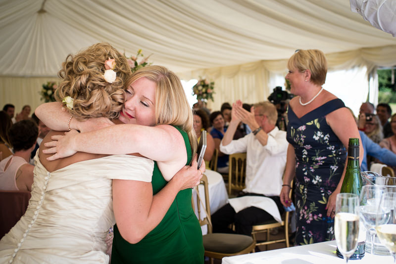 Bride hugs friend at Chiddingstone Castle wedding