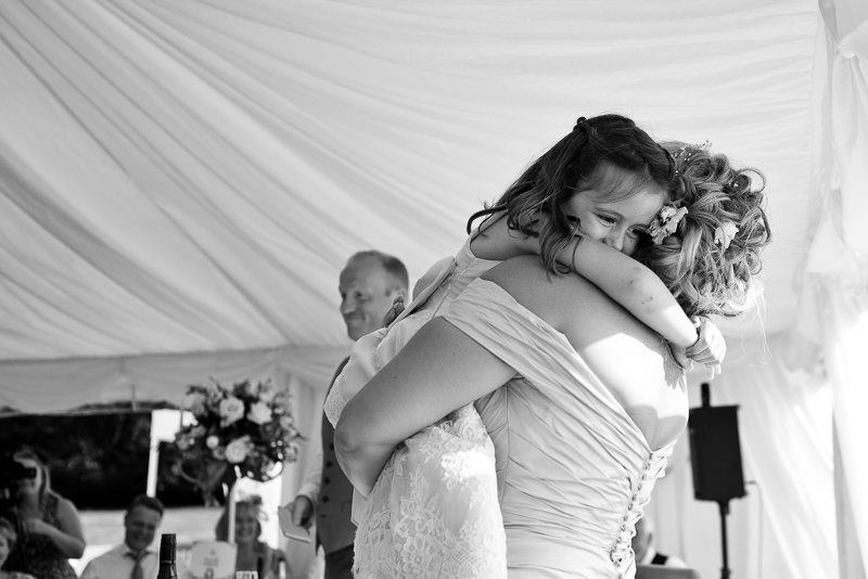 Bride hugs glower girl at Chiddingstone Castle wedding
