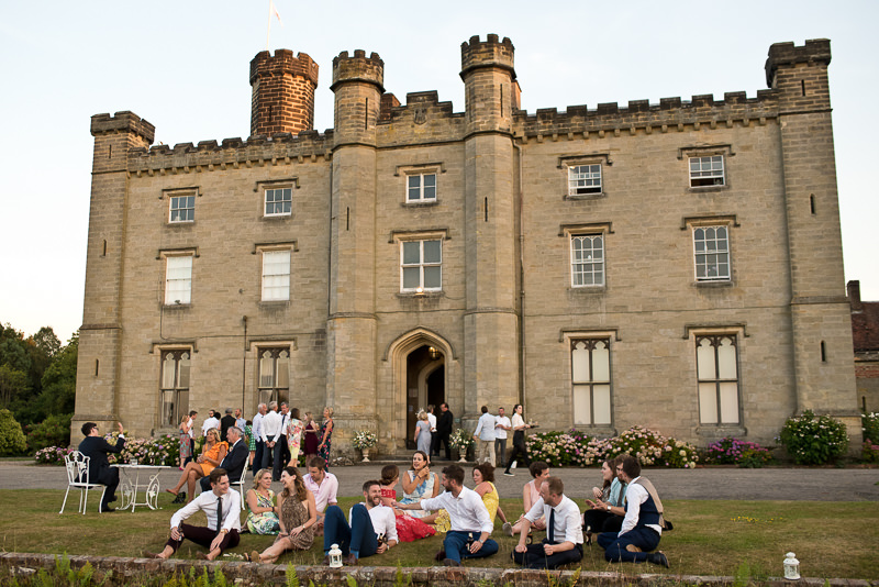 Wedding guests outside Chiddingstone Castle on a warm summer evening