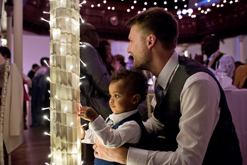 Groom with son looking at fairy lights at Amadeus Centre wedding