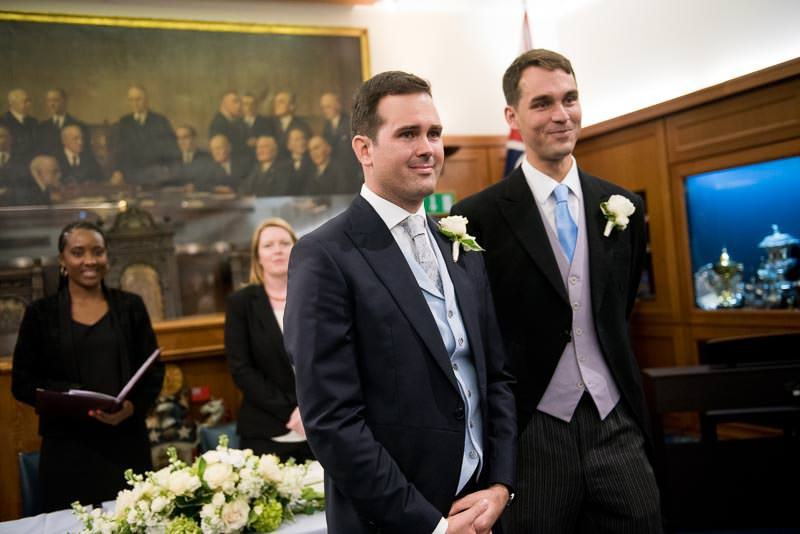 Groom watches bride walk up the aisle at HQS Wellington wedding