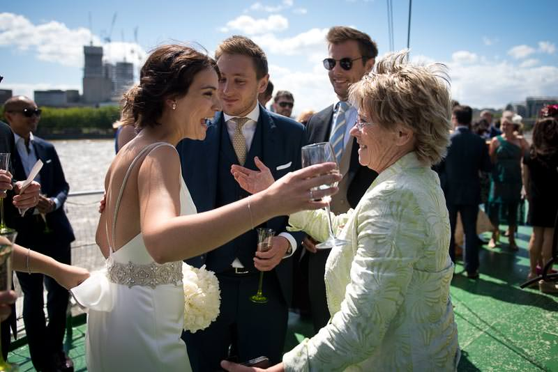 Bride greets guests at HQS Wellington wedding