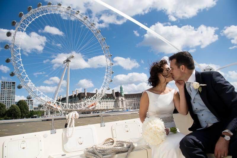 Bride and groom kiss in front of London Eye on water taxi