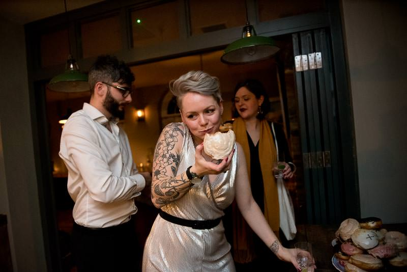 Bride eats vegan doughnuts at Cambridge Ktichen wedding reception
