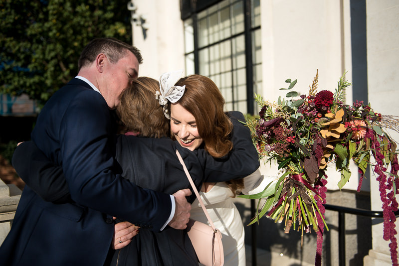 Bride and groom greet guests outside Islington Town Hall