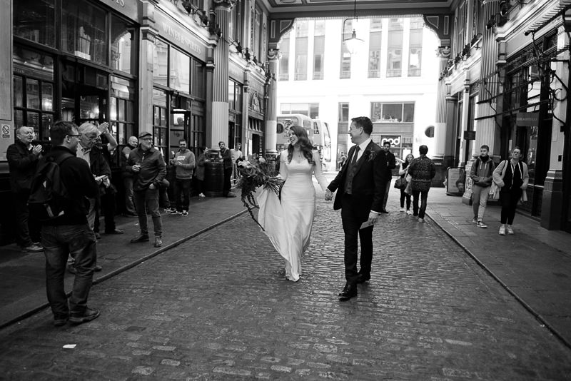 Bride and groom arrive for Leadenhall Market wedding. Bride in 1940s inspired dress made by Molly Quest.