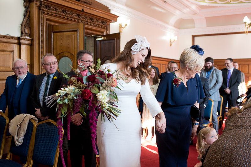 Bride walks up the aisle with Mum at Islington Town Hall