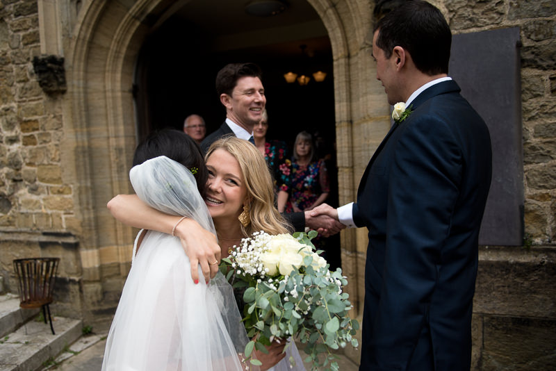 Bride greets guests outside St Mary's Church in Petworth