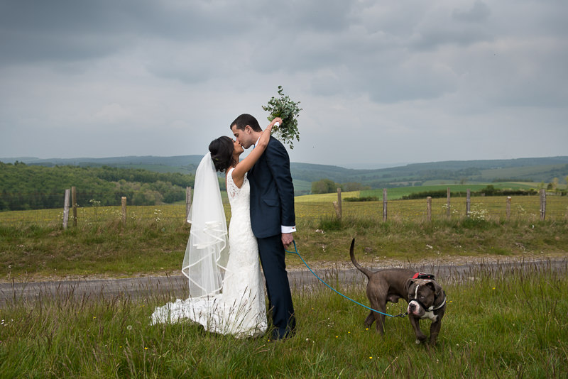 Bride and groom with dog in beautiful countryside