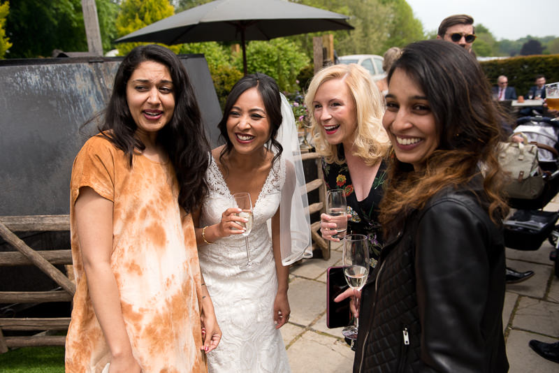 Bride mingles with guests during wedding drinks reception at the White Horse