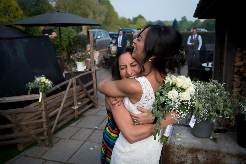 Bride hugs friend at wedding at the White Horse in Chichester
