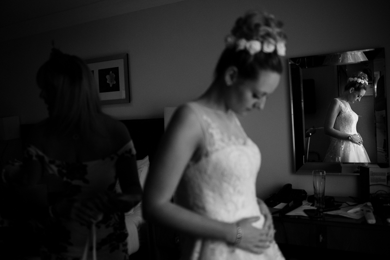 Pregnant bride puts on wedding dress