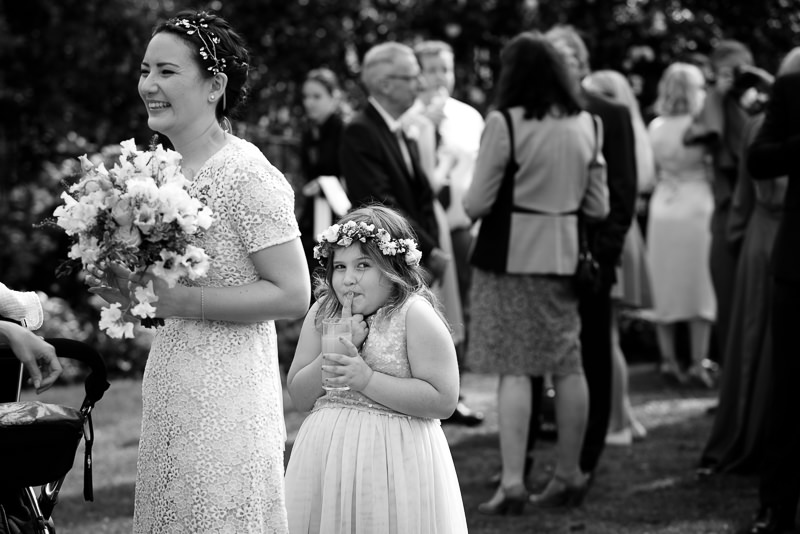 Black and white photograph of flower girl hiding behind bride taken by documentary wedding photographer