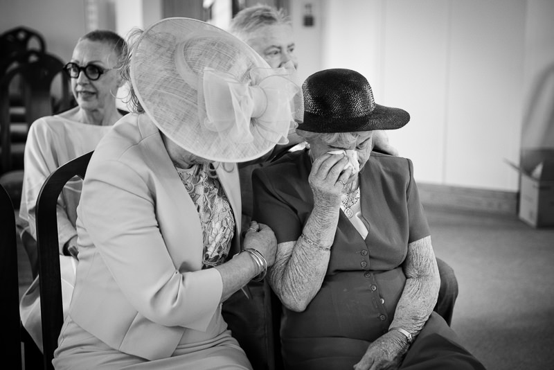 Documentary style wedding photo of grandma crying during wedding ceremony