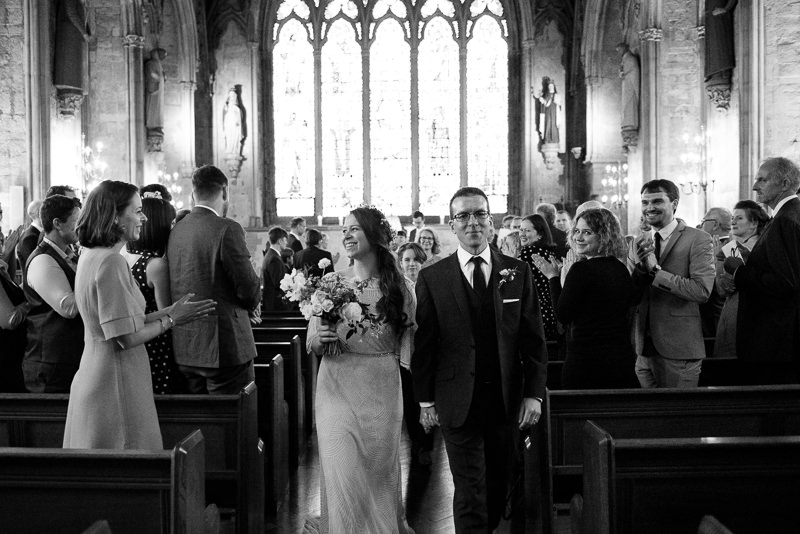 Bride and groom walk down the aisle at St Etheldreda wedding