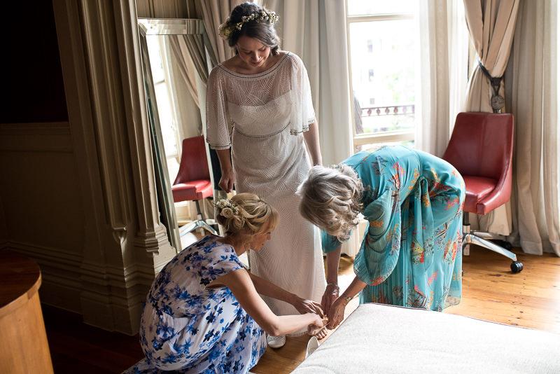 Bride puts on wedding dress at St Pancras Renaissance Hotel
