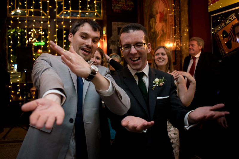 Groom and friend dancing the Macarena at pub wedding reception