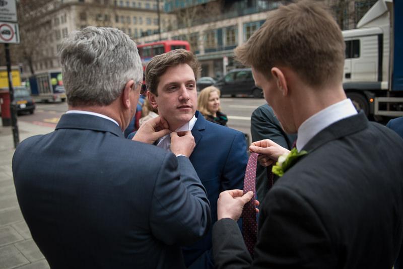 Groom ties tie on the steps of OldMarylebone Town Hall