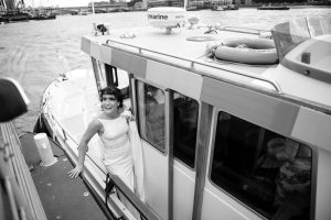 Black and white photograph of bride arriving at the HQS Wellington by River Taxi