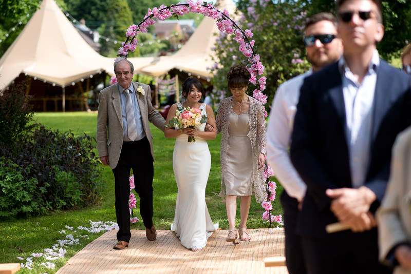 Bride walks up the aisle at outdoor wedding ceremony