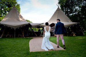 Bride and groom enter Tipi for wedding reception