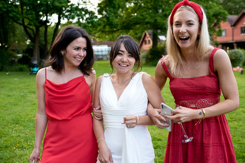 Bride with friends in red dresses at garden wedding