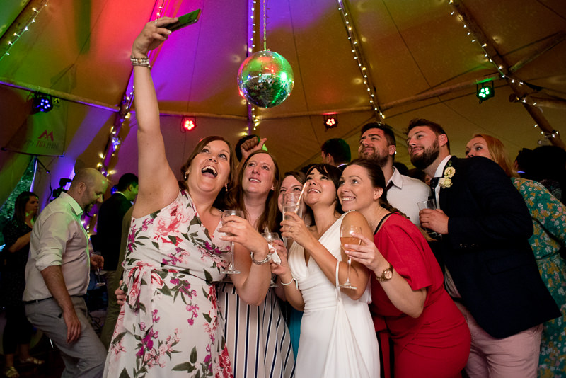 Guests and bride take selfie at Tipi wedding