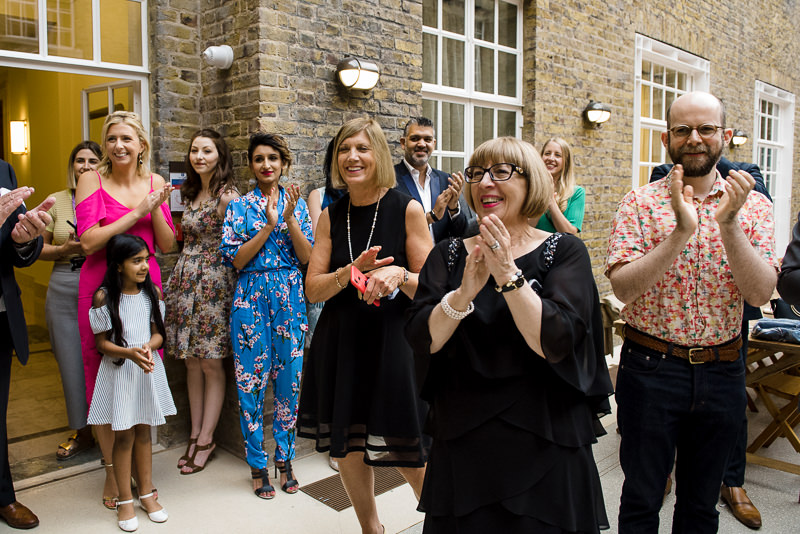 Guests cheer as couple gets married at the Atria in Hackney Town Hall
