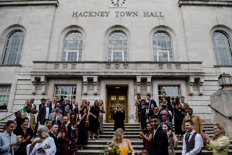 Bride in orange wedding dress outside Hackney Town Hall
