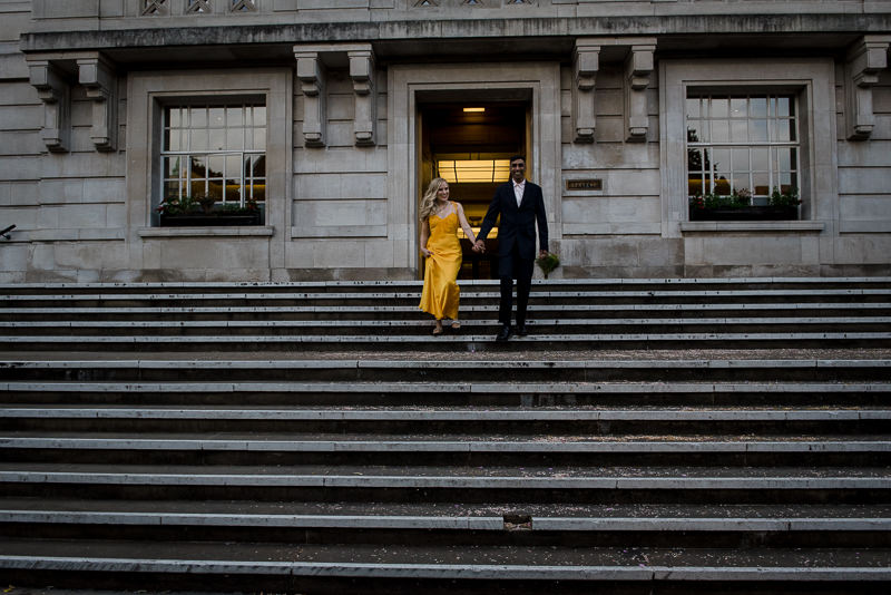 Bride in orange dress with groom on stairs at Hackney Town Hall