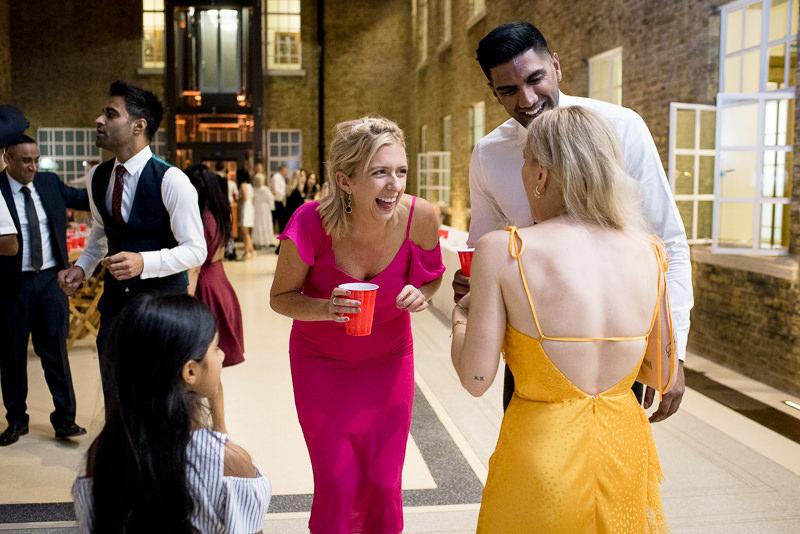 Guests laugh at Hackney Town Hall Atria wedding
