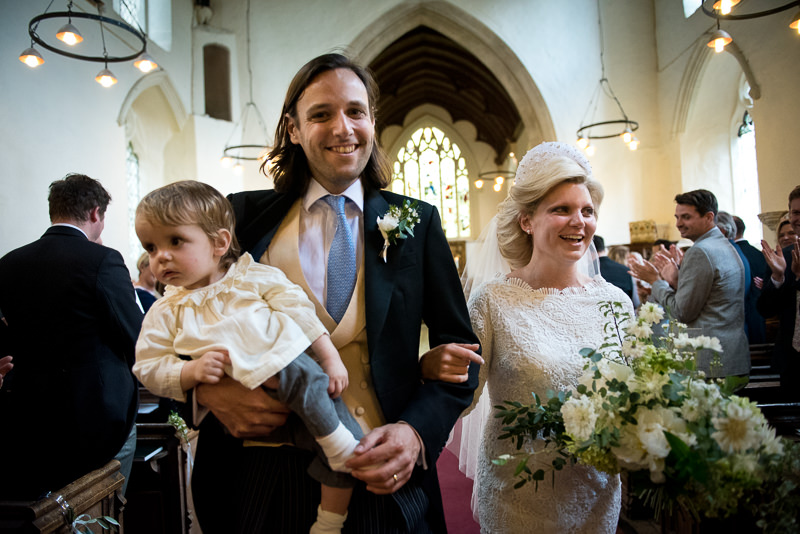 Bride, groom and son walk down the aisle at St Peter's church in Benington